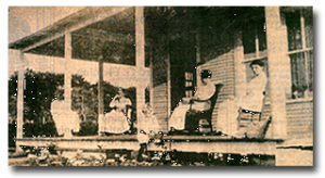 Historical photo of three women siting on rocking chairs on the front wrap around porch of the Ryckman House