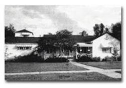 Historical Black and white photo of a long white house with dark trim