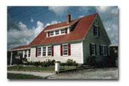 Historical Photo of The Red Bird House. a white building with red trim and an A line roof