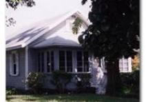 Photo of a small grey house with white trim. A tree is in the fron yard concealing part of the tree