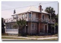 Historical photo of the Walter Brown PinkHouse, a two story home with first and second floor wrap around porches. The home is pink and has a chimney.